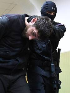 Zaur Dadayev is escorted by a policeman at the Basmanny district court in Moscow